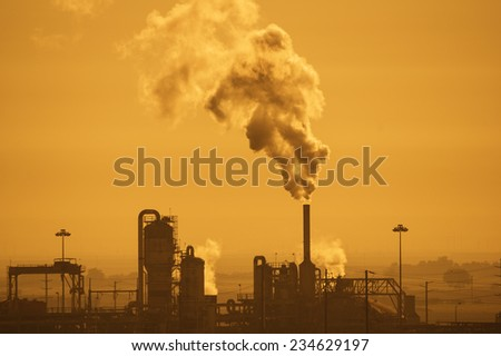 industrial plant with air pollution in a hazy orange sky - stock photo