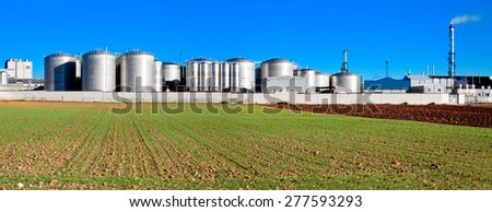 industrial plant with store buildings near field  - stock photo