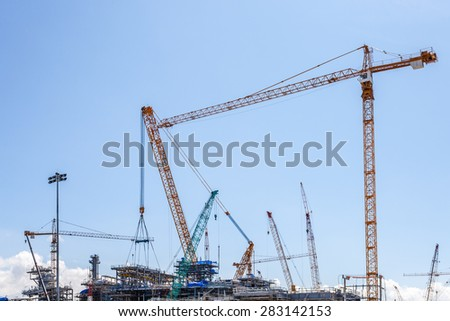 Industrial plants are currently under construction with many tower cranes and worker - stock photo