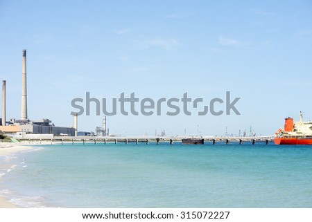 Industrial production plant with factory buildings, high rising chimneys at ocean beach, bulk cargo vessel at dock of port, sunny blue sky, copy space. - stock photo