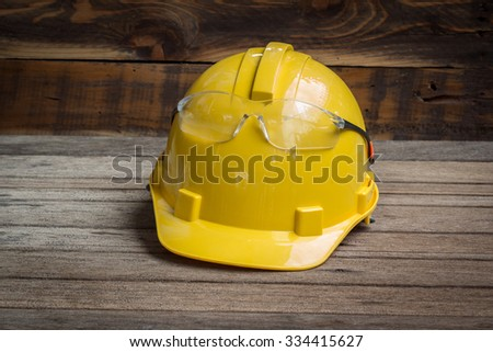 Industrial Protective Workwear. Includes Hard Hat and safety glasses on wooden - stock photo