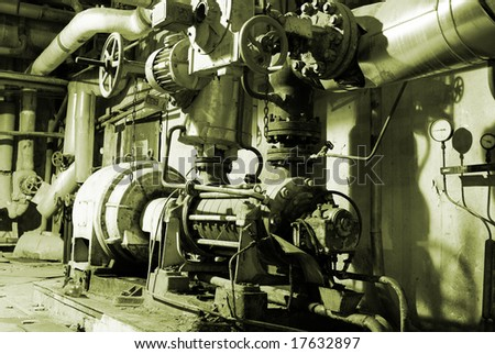 industrial pumps and pipelines in factory - stock photo