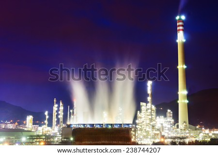 industrial refinery at night with cooling water smoke - stock photo
