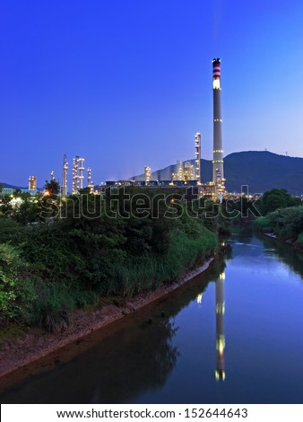 industrial refinery with smokestack near a river - stock photo