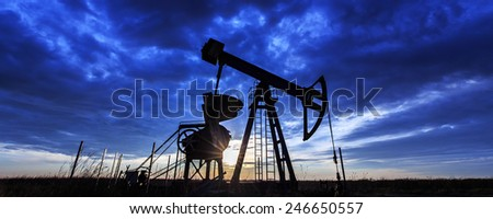Industrial scenery with oil and gas well pump, profiled on sunset sky - stock photo
