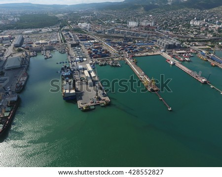 Industrial seaport, top view. Port cranes and cargo ships and barges. Loading and shipment of cargo at the port. View of the sea cargo port with a bird's eye view. - stock photo