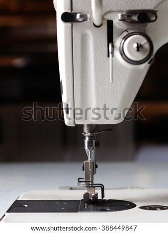 industrial sewing machine in a textile fashion design school factory close up details - stock photo