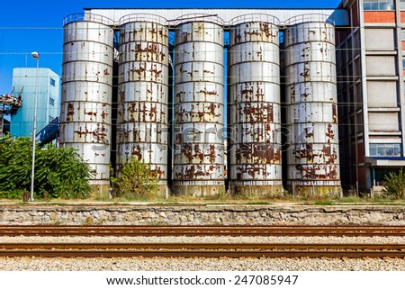 Industrial Silo, in background, behind parallel railroad tracks. - stock photo