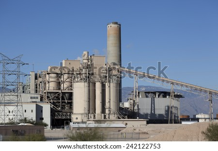 Industrial site with smoke pipe, elevator and power lines running through blue sky - stock photo