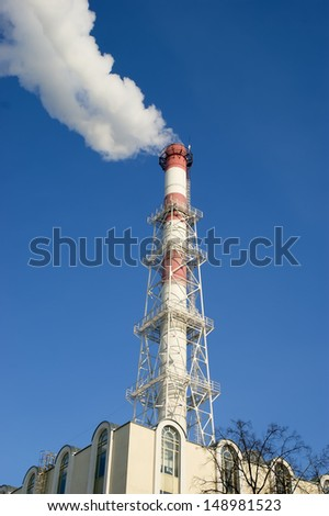 Industrial smokestacks with billowing white smoke being pumped into the atmosphere against a blue sky - stock photo