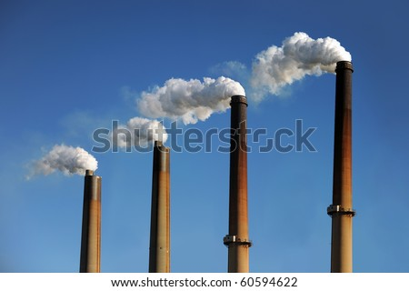 Industrial smokestacks with smoke clouds over blue sky - stock photo