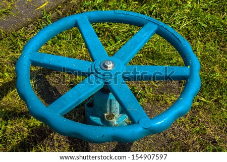 Industrial tap on the ground against grass - stock photo