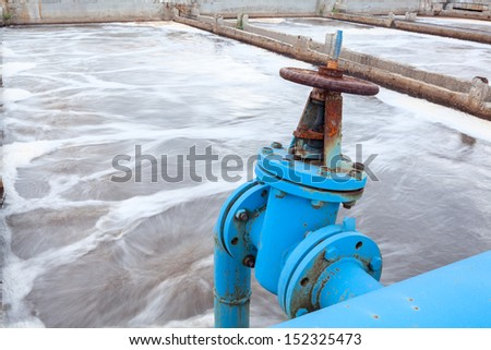 Industrial tap with blue pipeline for oxygen blowing into sewage water - stock photo