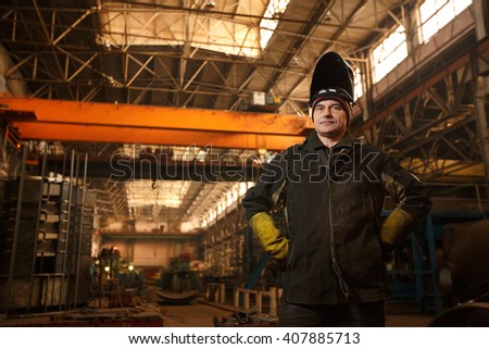 Industrial theme: businessman at a manufacturing area. Portrait. The man working the plant or factory. Pour the metal in a workshop or hangar. - stock photo