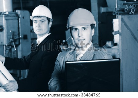 Industrial theme: two blue collars at a manufacturing area. - stock photo