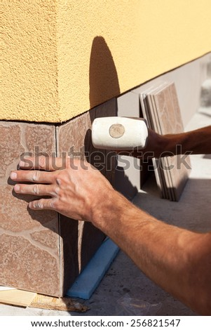 Industrial tiler builder worker installing tile - stock photo