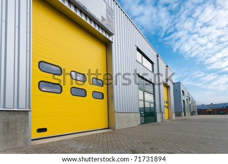 industrial warehouse with green and yellow roller doors - stock photo