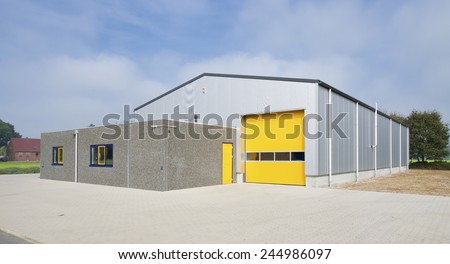 industrial warehouse with yellow roller door - stock photo