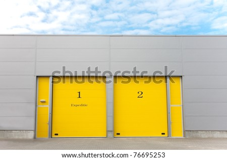 industrial warehouse with yellow roller doors - stock photo