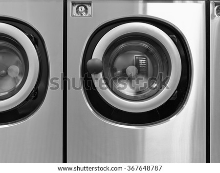 Industrial washing machines in a public laundromat from front - stock photo