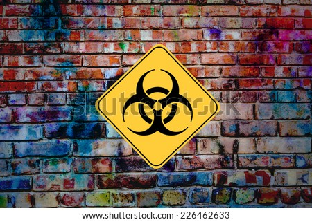 Industrial Waste. Biohazard or Bio Hazard symbol sign on old graffiti wall of defunct factory - stock photo