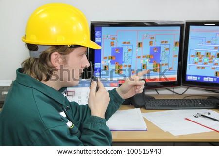 Industrial worker in control room - stock photo