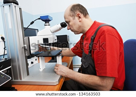 industrial worker in uniform checking quality of processed metal probe using precise optical industrial microscope - stock photo
