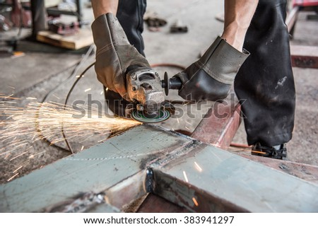 Industrial worker is removing the welding line to make it smooth - stock photo