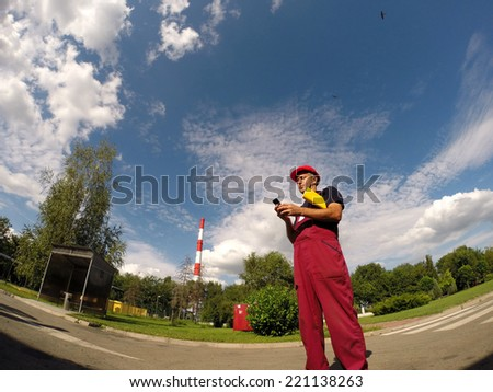 Industrial Worker Looking at His Cell Phone.Industrial worker standing in factory premises and looking at cell phone. - stock photo
