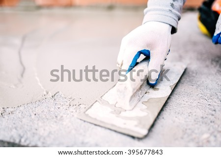 industrial worker on construction site laying sealant for waterproofing cement - stock photo