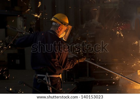 Industrial worker on iron melting plant - stock photo