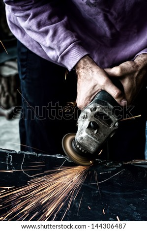 industrial worker using a small grinder for cutting metal in steel factory - stock photo