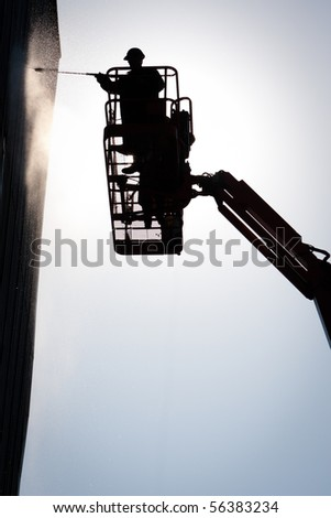 industrial worker wash building with high pressure water - stock photo