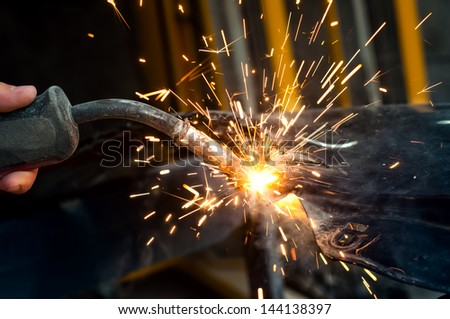 industrial worker welding metal in steel factory with sparks - stock photo