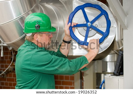 Industrial worker with a big blue screw - stock photo