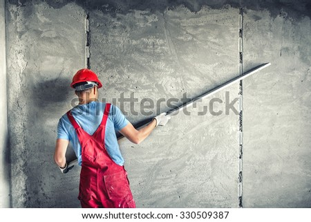 industrial worker with plastering tools renovating a house. builder worker plastering facade industrial building with leveler - stock photo