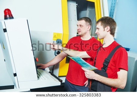 industrial workers at cnc turning machine center in tool manufacture workshop - stock photo