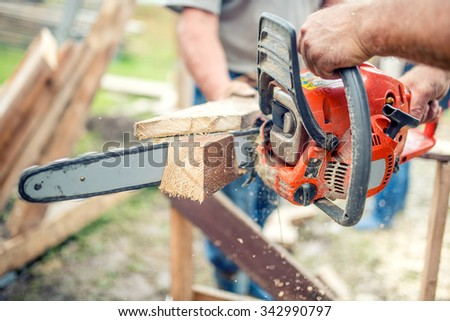 industrial workers cutting timber wood with chainsaw. Men sawing using electrical chainsaw - stock photo