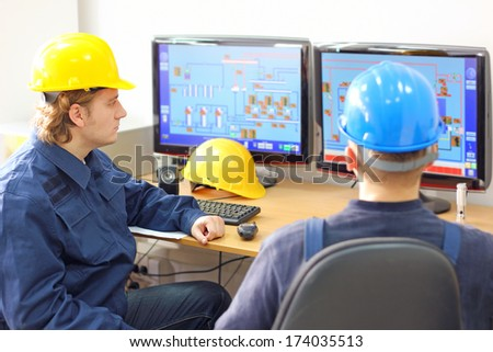 Industrial workers in control room - stock photo