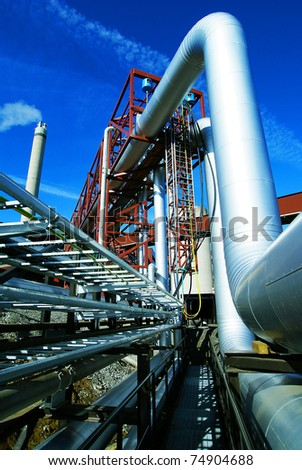 Industrial zone, Steel pipelines, smokestack and valves against blue sky - stock photo