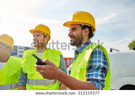 industry, building, technology and people concept - happy male builders in high visible vests with walkie talkie or radio outdoors - stock photo