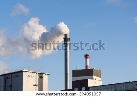 industry chimney with smoke and factory buildings against the blue sky with copy space - stock photo
