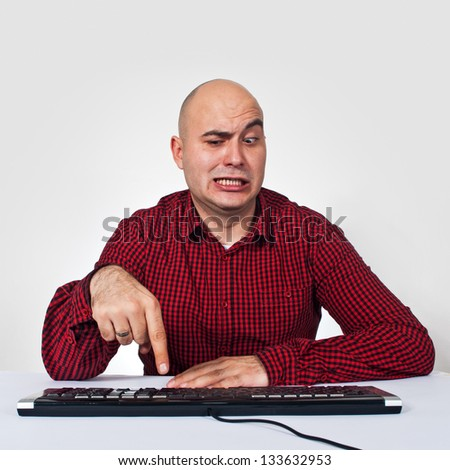 Inexperienced computer user. Man sitting at the table with keyboard in front of the computer having problems with software - stock photo