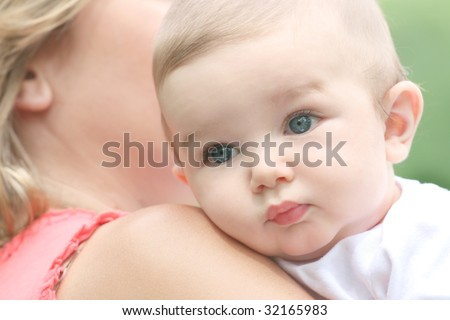 Infant baby boy in mother's arms - stock photo