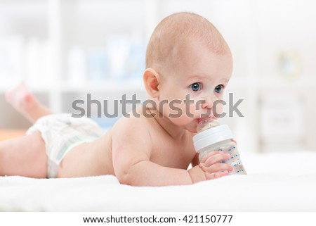 Infant baby drinking water from bottle lying on bed. Child weared diaper in living room. - stock photo