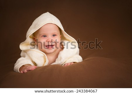 Infant baby in towel on brown background - stock photo