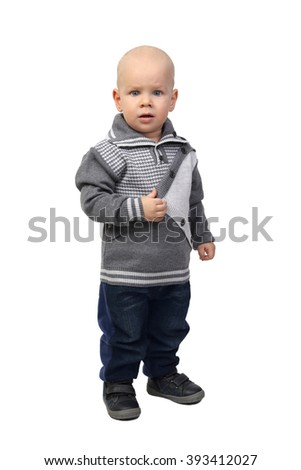 Infant baby in warm clothes standing serious full height isolated on white background - stock photo