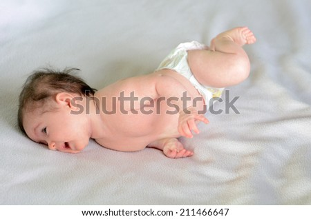Infant baby roll over in bed.Concept photo of infant baby childhood healthcare development. Copy space - stock photo