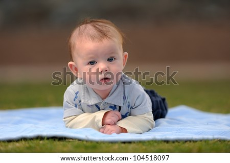 Infant Boy Laying on Front Outside. Infant three-month old boy laying on a blanket outside while looking at the viewer. Shallow DOF. - stock photo