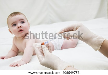 Infant child baby kid creep and hand with medical insulin syringe ready for injection  - stock photo